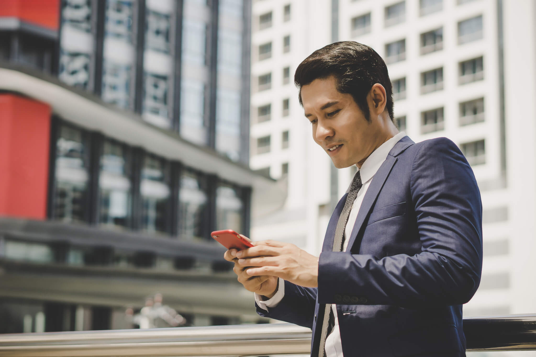 Portrait of happy businessman using telephone outdoors